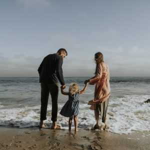 child with parents at the sea side